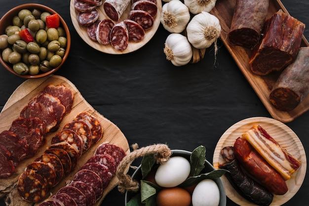 Knoblauch und eier nahe würsten und oliven