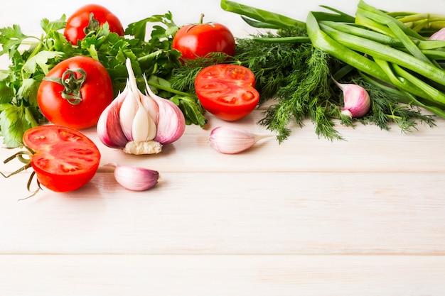 Knoblauch und tomate auf dem weißen hölzernen