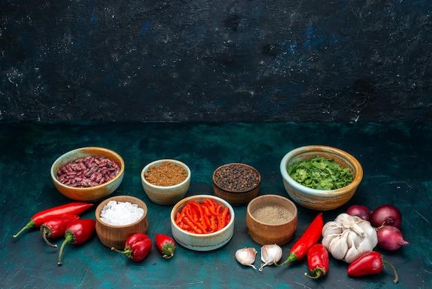 Knoblauch und zwiebeln zusammen mit paprika, gemüse und gewürzen auf dunklem, pflanzlichem pfeffer