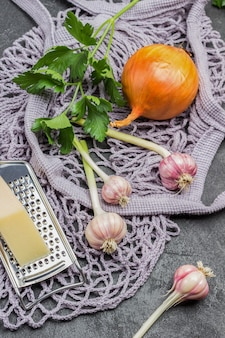 Knoblauch, zwiebel und käse auf reibe, petersilie. tasche aus netzstoff mit lebensmitteln. schwarzer hintergrund. ansicht von oben Premium Fotos