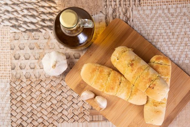 Knoblauchbrot gefüllt mit käse auf einem schneidebrett mit knoblauch und einer flasche olivenöl angeordnet