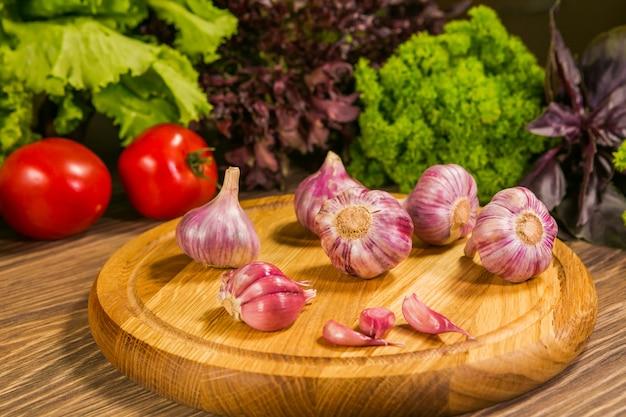 Knoblauchknollen auf einem hölzernen brett mit einem grünen salat