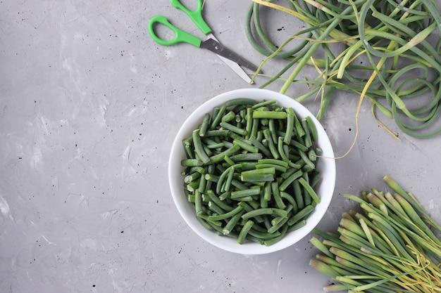 Knoblauchpfeile zum kochen auf tisch und scheiben in der schüssel auf grauem betonhintergrund. zutat für fernöstliches essen.