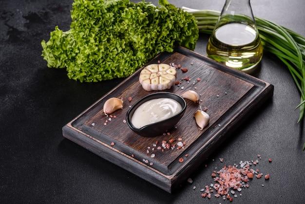 Knoblauchsauce in einer schwarzen keramiksauce mit grün auf einem hölzernen schneidebrett auf einem dunklen betontisch