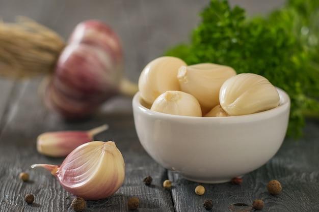 Knoblauchzehen in einer weißen schüssel und ungeschälter knoblauch auf dem tisch. gesunde natürliche gewürze. bestandteil der traditionellen medizin.