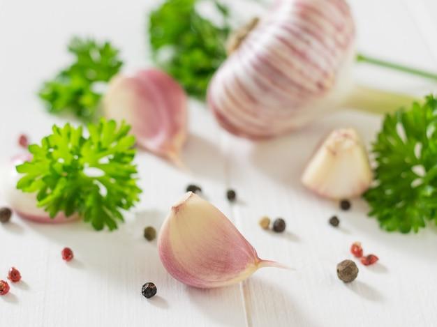 Knoblauchzehen und ein ganzer knoblauch mit gewürzen auf einem weißen holztisch. gesunde natürliche gewürze. bestandteil der traditionellen medizin.