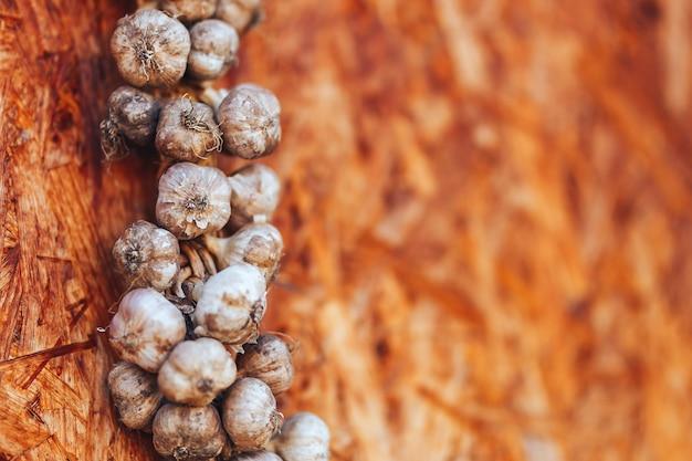 Knoblauchzopf auf dem hölzernen hintergrund, der in der ecke hängt