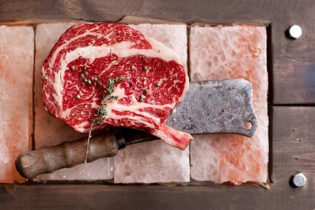 Knochen im rib-eye-row-steak auf salzstücken auf holzbrett