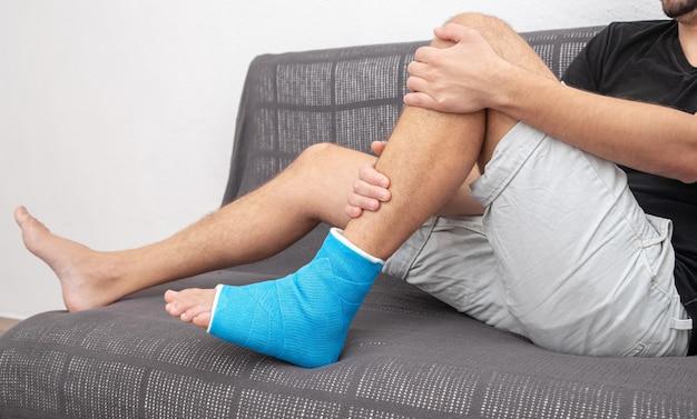 Knochenbruch fuß und bein bei männlichem patienten und orthopädische genesung auf dem sofa liegend am blauen schienenknöchel.
