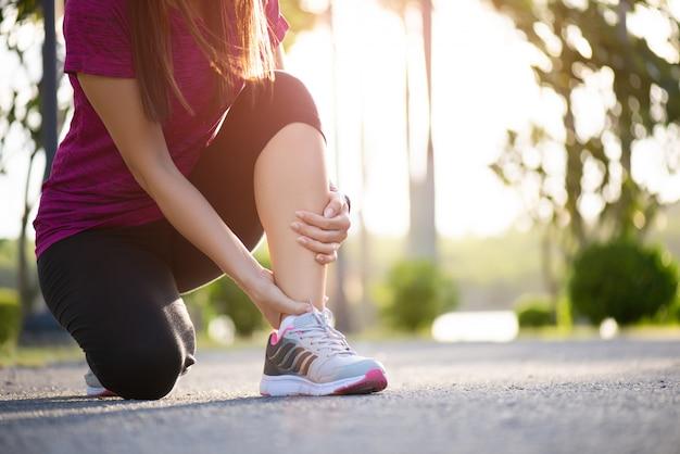 Knöchel verstaucht. frau, die unter einer knöchelverletzung beim trainieren leidet