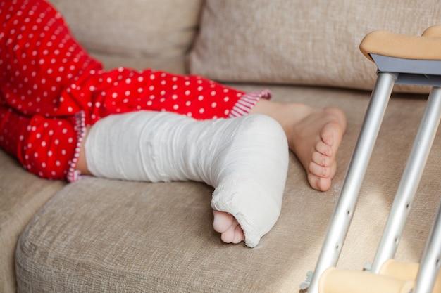 Knöchelbruch bei einer patientin im teenageralter mit gipsverband und krücken