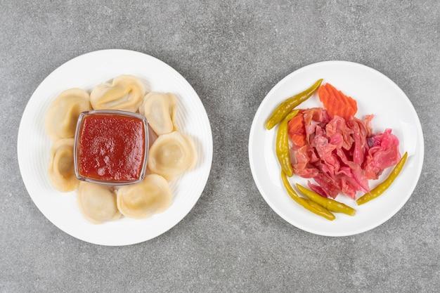 Knödel gefüllt mit fleisch und teller mit eingelegtem gemüse