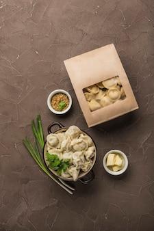 Knödel in umweltfreundlicher papierverpackung zur lieferung und eine schüssel mit knödeln, zwiebeln und saucen