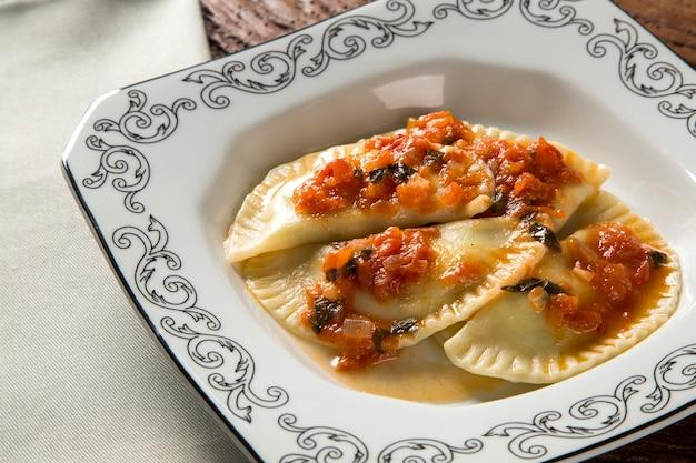 Knödel mit fleisch mit tomaten auf einem teller - pierogi