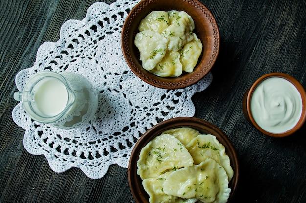 Knödel mit kartoffeln und kohl. saure sahne, milch und gemüse.
