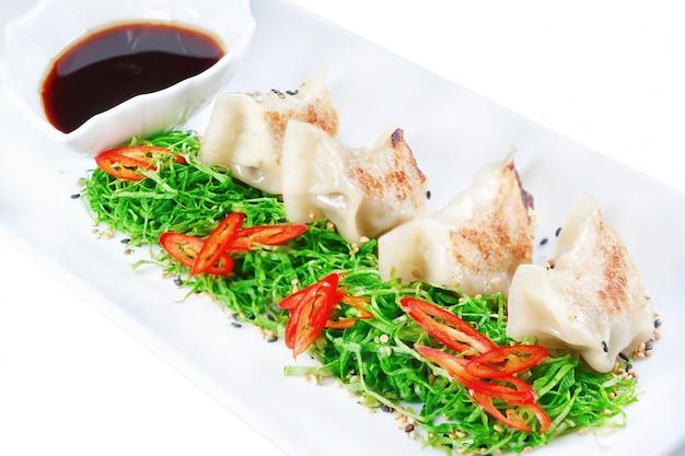 Knödel, ravioli gefüllt mit meeresfrüchten aus der nähe. mit schwarzem essig.