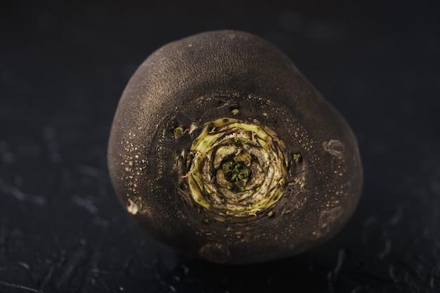 Knollenschwarz rettich auf einer schwarzen betonoberfläche