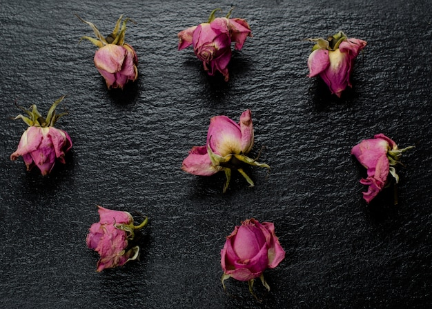 Knospen von rosa verblassten trockenen rosen verstreut auf einem schwarzen schieferhintergrund