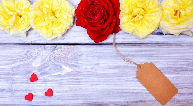 Knospen von rosen und von papier etikettieren auf einem seil