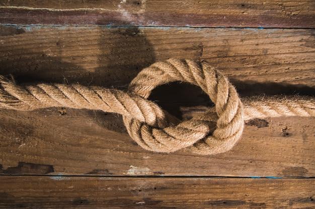 Knoten an einem seil auf einer holzoberfläche.