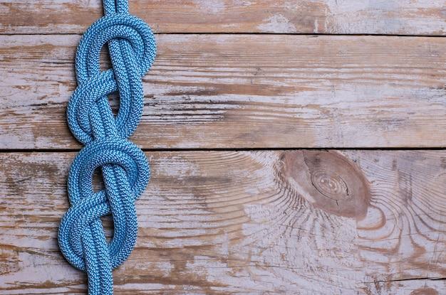 Knoten in form einer acht an einem seil auf einem hölzernen hintergrund. speicherplatz kopieren.