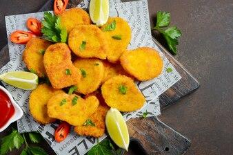 Knusperige Fried Chicken Nuggets mit Tomatensauce auf dunklem Hintergrund