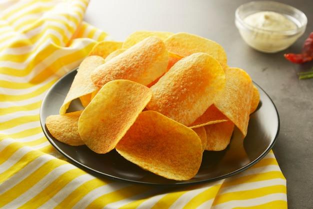 Knusperige kartoffelchips lokalisiert über grauem strukturiertem