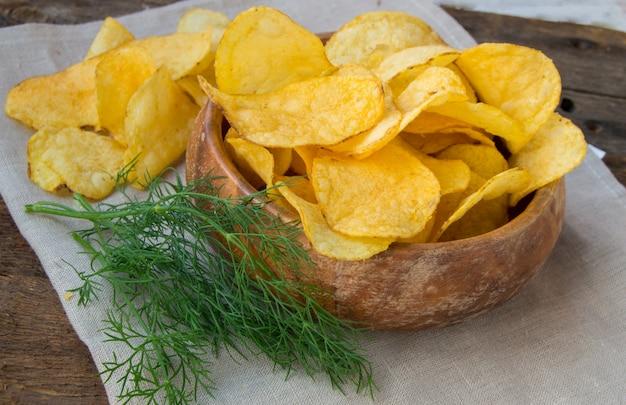 Knusperige kartoffelchips mit dill in einer hölzernen schüssel auf leinenserviette