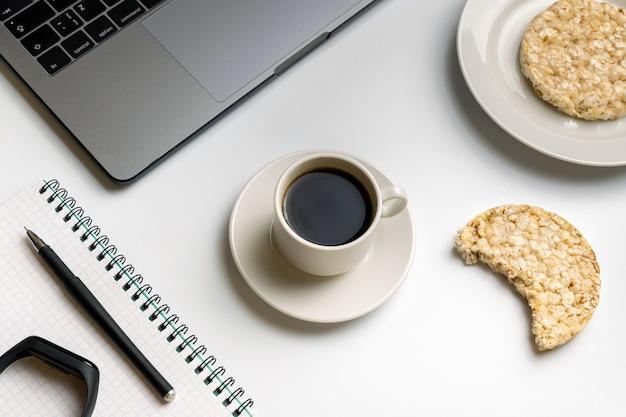 Knusperige reisrunden mit kaffee in der nähe von laptop und notebook.