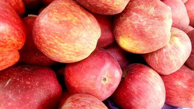 Knusperiger apfelhintergrund des neuen ausgewählten roten honigs in der erntezeit gelegt in einen markt oder in einen basar für verkauf