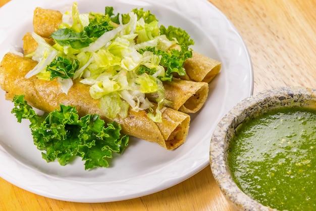 Knusperiger fried tacos mit kopfsalat und salsa, mexikanisches lebensmittel