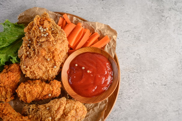 Knusperiges gebratenes huhn auf einer hölzernen platte mit tomatensauce und karotte
