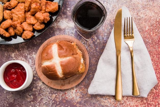 Knusperiges hühnerpopcorn mit burger und alkoholfreiem getränk auf verwittertem hintergrund