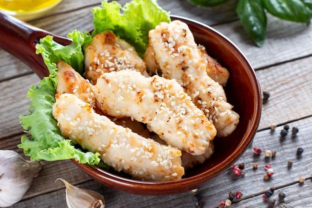 Knusprig frittierte hühnerstreifen mit sesam auf rustikalem holzhintergrund