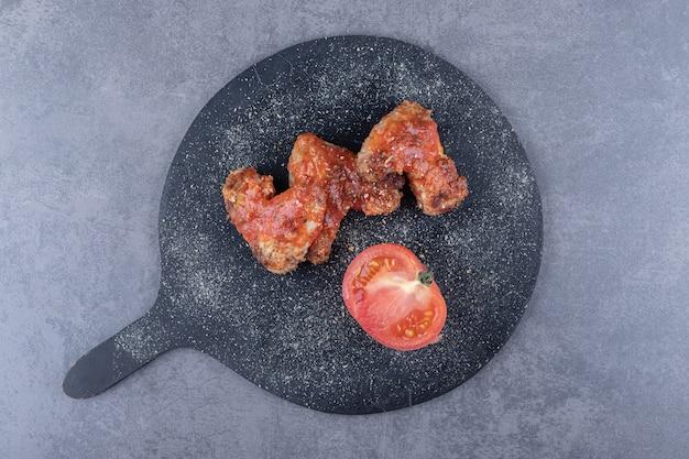 Knusprig gebratene flügel und tomate auf schwarzem brett.