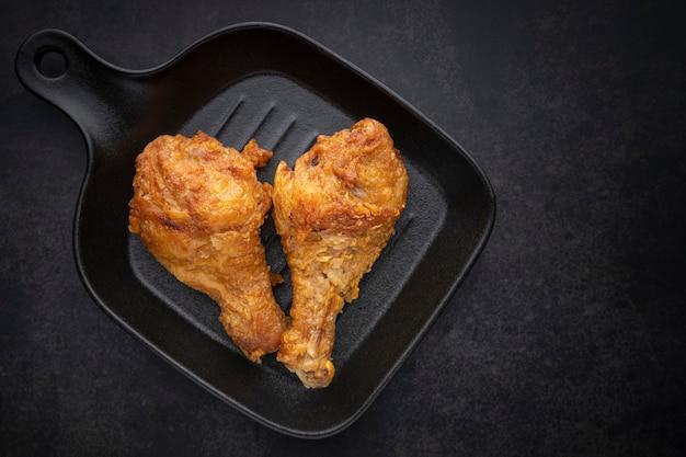 Knusprig gebratener hühnerkeulenstock in schwarzer pfanne auf dunklem hintergrund, ansicht von oben