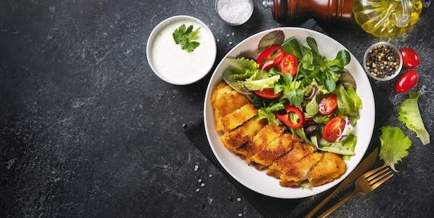 Knusprig panierter kabeljau mit salat in einem teller