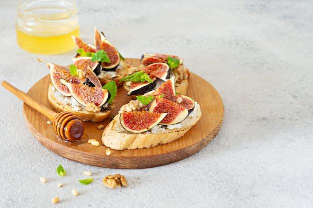 Knusprige bruschetta mit weichem ricotta, reifen feigen, walnüssen und pinienkernen, minze und honig auf hellem hintergrund.