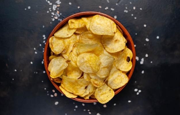 Knusprige chips in einer schüssel auf einem steinhintergrund
