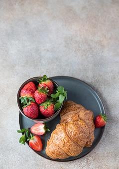 Knusprige croissants mit erdbeere auf einem teller und beeren in einer schüssel
