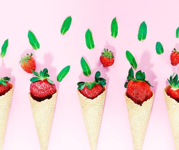 Knusprige eistüten mit erdbeere auf heller oberfläche