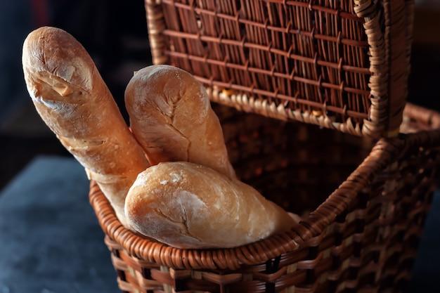 Knusprige, frisch gebackene französische baguettes in einem einkaufskorb auf dem tisch. selektiver fokus.