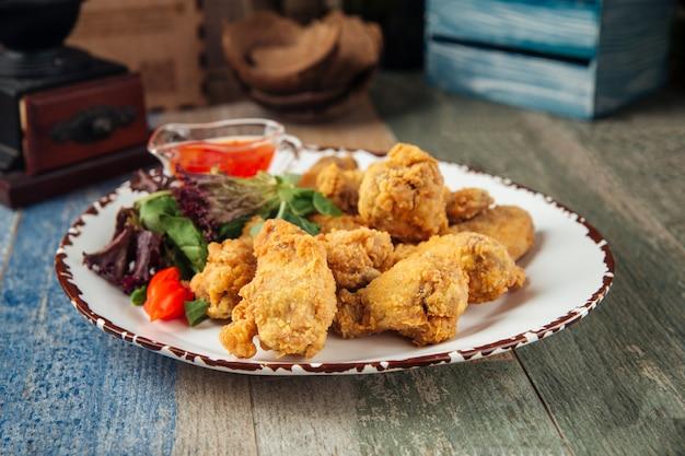 Knusprige frittierte hühnerflügel mit gemüse