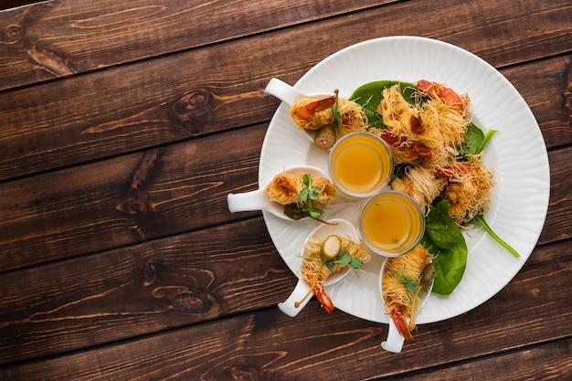 Knusprige garnele in kataifi-kruste und thymian mit champagne sauce in den gläsern liegen auf einer weißen platte auf einem waldigen hintergrund. freier platz für text