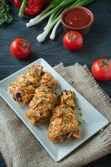 Knusprige gebratene hähnchenschenkel paniert mit pommes. gebackene drumsticks sind mit gemüse und kräutern dekoriert. fast food. falsches essen. dunkler hölzerner hintergrund.