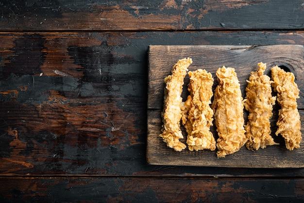 Knusprige gebratene hühnerbratenschnitte auf altem dunklem holztisch, draufsicht.