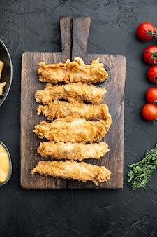 Knusprige gebratene hühnerbratenschnitte auf schwarzem hintergrund