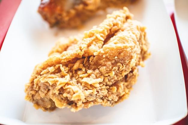 Knusprige gebratenes hühnchen-junk-food im papierkasten eines franchise-cafés.