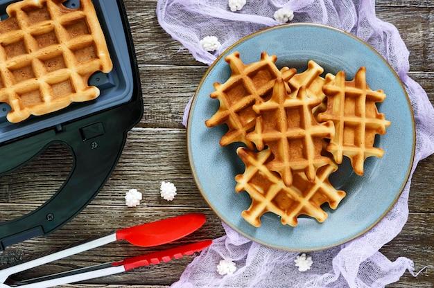 Knusprige goldene vanille-waffeln mit birnenmarmelade, elektrische waffelschale auf einem hölzernen hintergrund. draufsicht.