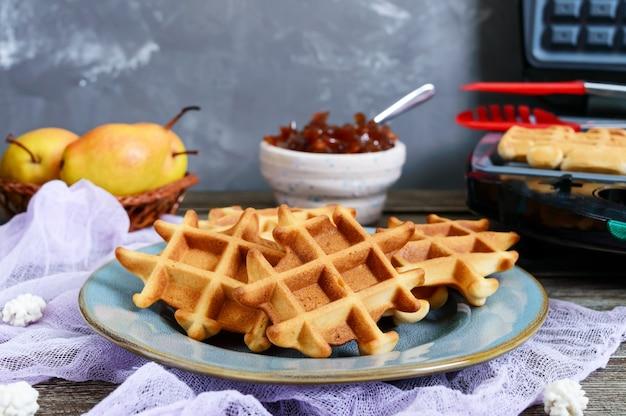 Knusprige goldene vanille-waffeln mit birnenmarmelade, elektrische waffelschale auf einem hölzernen hintergrund.